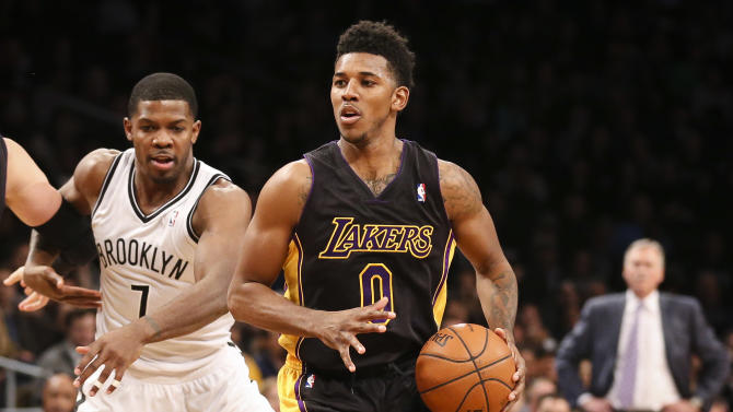 Los Angeles Lakers small forward Nick Young (0) dribbles past Brooklyn Nets shooting guard Joe Johnson (7) in the fourth quarter of an NBA basketball game at the Barclays Center, Wednesday, Nov. 27, 2013, in New York. The Lakers defeated the Nets 99-94