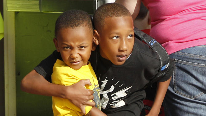 Cam'ron Richardson, right, hugs his little brother Anthony Richardson, left, as he heads in for the first day of school at Plaza Towers Elementary school in their temporary location at Central Jr. High school in Moore, Okla., Friday, Aug. 16, 2013. The Briarwood and Plaza Towers elementary schools were destroyed when an EF5 twister hit Moore on May 20. Cam'ron was trapped under the rubble of the tornado that killed two dozen people. (AP Photo/Sue Ogrocki)