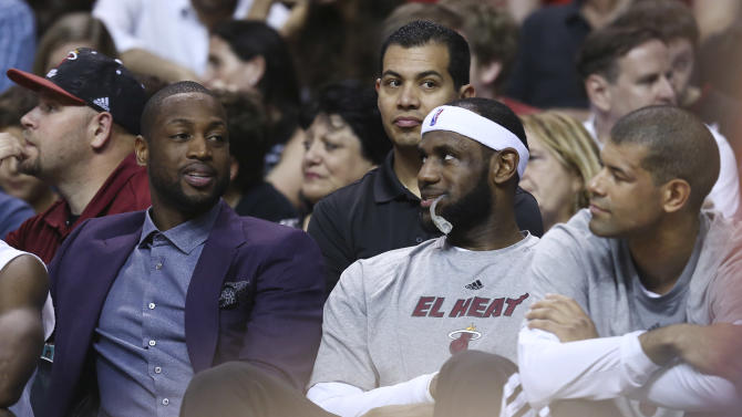 Miami Heat players Dwyane Wade, left, talks to LeBron James, and Shane Battier during the first half of an NBA basketball game in Miami, Monday, March 3, 2014 against the Charlotte Bobcats. Wade did not play in the game. (AP Photo/J Pat Carter)