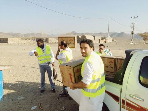 Boy Scouts participating in the Messengers of Peace workshop at King Abdullah Economic City distribute food baskets to the needy families. — Courtesy photo
