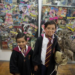 Harry Potter fans Mateo Lara, 5, right, and his brother Francisco, 7, pose for photos with a live owl inside an exhibition of the Guinness World Record holding collection of Harry Potter memorabilia, at the Mexican Museum of Antique Toys, in Mexico City, Friday, Feb. 27, 2015. Mexico's fan Menahem Asher Silva Vargas assembled the collection, which contains thousand objects, including figurines, wands, magazines, puzzles, and accessories. (AP Photo/Rebecca Blackwell)