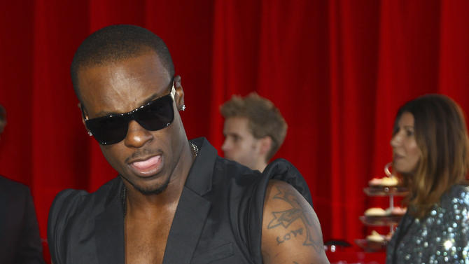 Tim Omaji, better known by his stage name Timomatic, arrives for the Australian music industry Aria Awards in Sydney, Thursday, Nov. 29, 2012. (AP Photo/Rick Rycroft)