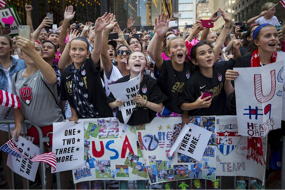 Fans of the U.S. women's soccer team cheer during the ticker tape parade to celebrate their World Cup final win over Japan on Sunday, in New York