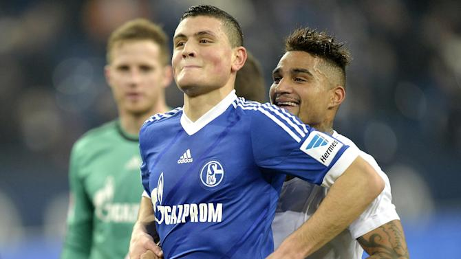 Schalke's Kyriakos Papadopoulos, left, is pushed to the fans by Schalke's Kevin-Prince Boateng, right, after the German Bundesliga soccer match between FC Schalke 04 and SC Freiburg in Gelsenkirchen, Germany, Sunday, Dec. 15, 2013