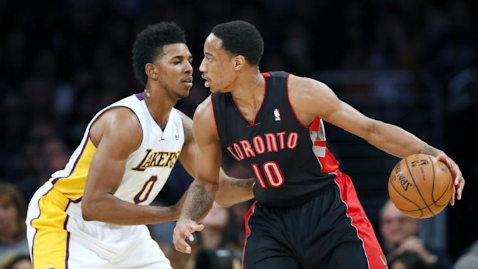 Toronto Raptors' DeMar DeRozan, right, controls the ball as Los Angeles Lakers' Nick Young, left, defends during the first half of an NBA basketball game in Los Angeles, Sunday, Dec. 8, 2013