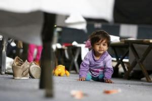 A migrant child looks on as it sits on the ground at…