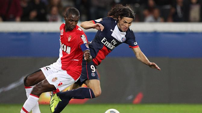 Paris Saint Germain's forward Edinson Cavani from Uruguay, centre,  challenges for the ball with Monaco's defender Eric Abidal, during their French League One soccer match, at the Parc des Princes stadium, in Paris, Sunday, Sept. 22, 2013