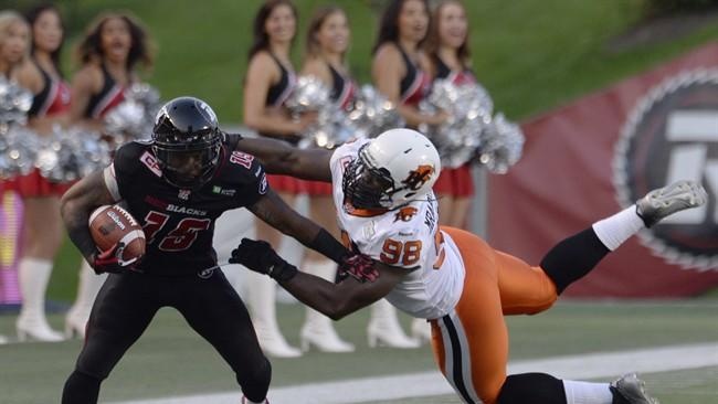 Ottawa Redblacks' Jock Sanders (19) is stopped B.C. Lions' Ese Mrabure-Ajufo (98) as he runs back a punt return during second half CFL action in Ottawa on Saturday July 4, 2015. THE CANADIAN PRESS\Adrian Wyld