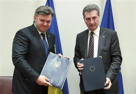Ukrainian Energy and Fuel Minister Eduard Stavytsky (L) stands with European Energy Commissioner Guenther Oettinger after signing an agreement on energy cooperation at an EU-Ukraine summit in Brussels February 25, 2013. REUTERS/Olivier Hoslet