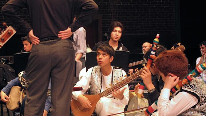 Young musicians from a school in Kabul, Afghanistan, rehearse for a Carnegie Hall concert with musicians from Scarsdale High School in Scarsdale, N.Y., on Monday, Feb. 11, 2013. The Afghan Youth Orchestra, many of whose members are not far removed from eking out a living on the streets of Kabul, is on the New York leg of a U.S. tour that melds Western classics with traditional Afghan music. About 50 players held a joint rehearsal Monday with 25 members of the Scarsdale High School orchestra, which meant that young musicians from a war-torn country where music was banned for several years by the Taliban were playing alongside those from one of New York's toniest suburbs. (AP Photo/Jim Fitzgerald)