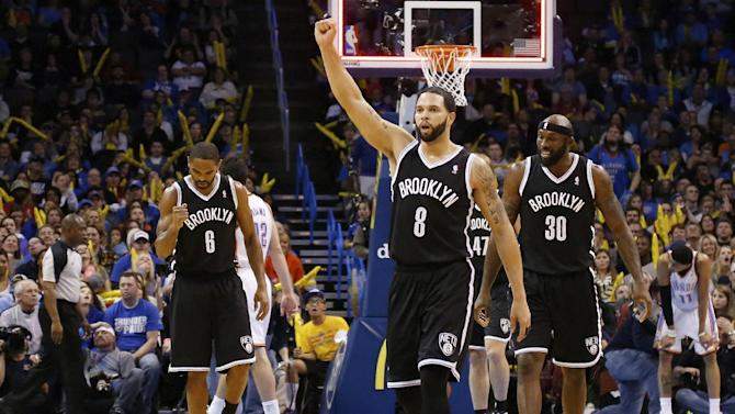 Brooklyn Nets guard Alan Anderson (6), guard Deron Williams (8) and forward Reggie Evans (30) celebrate as they walk off the court at the end of the third quarter of an NBA basketball game against the Oklahoma City Thunder in Oklahoma City, Thursday, Jan. 2, 2014. Oklahoma City won 95-93