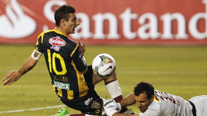 Escobar of Bolivia's The Strongest fights for the ball with goalkeeper Carvallo of Peru's Universitario during Copa Libertadores match in Lima