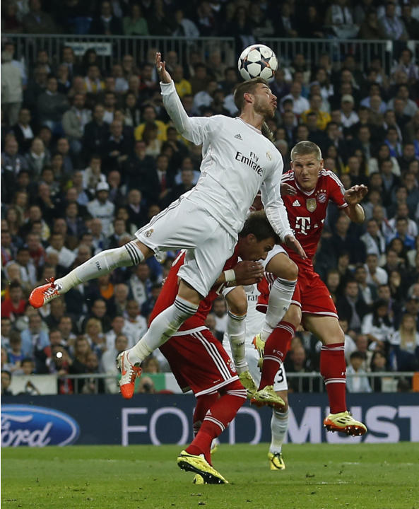 Real's Sergio Ramos jumps for the ball with Bayern's Bastian Schweinsteiger and Mario Mandzukic, during a first leg semifinal Champions League soccer match between Real Madrid and Bayern Munic