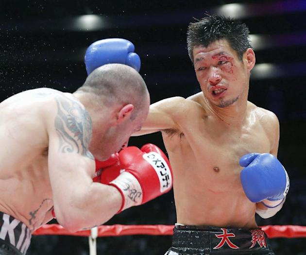 Spanish champion Kiko Martinez ducks a punch of Japanese challenger Hozumi Hasegawa, right, in the fifth round of their IBF super bantamweight boxing title bout in Osaka, western Japan, Wednesday, Apr
