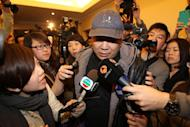A relative of a passenger on board missing Malaysia Airlines flight MH370 is surrounded by journalists in a hotel in Beijing, March 9, 2014