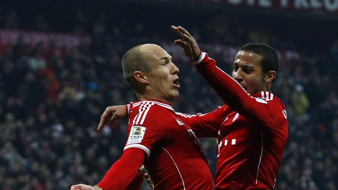 Bayern Munich's Robben and Thiago jump in air while celebrating a goal during German Bundesliga first division soccer match against Schalke 04 in Munich