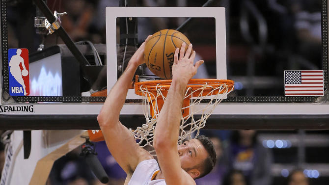 Phoenix Suns' Miles Plumlee (22) dunks as Memphis Grizzlies' Zach Randolph (50) defends during the first half of an NBA basketball game on Thursday, Jan. 2, 2014, in Phoenix
