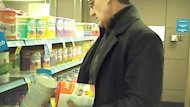 A CBC producer using a hidden camera records reporter Eric Rankin checking expiry dates on infant formula in a Vancouver-area supermarket.
