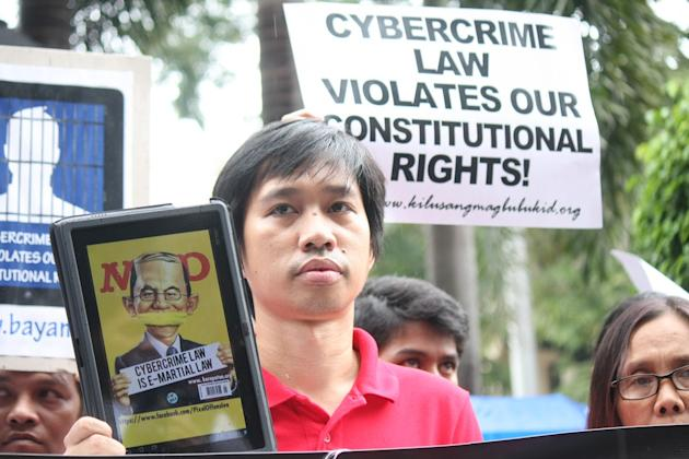 A protester displays a placard and wears a tape over his mouth during a rally against the new Anti-Cybercrime Law by the Aquino government, at the Supreme Court in Manila, on 02 October 2012. The Supreme Court is set to tackle during its en banc session today several petitions questioning the constitutionality of certain provisions of Republic Act (RA) 10175, or the Cybercrime Prevention Act of 2012. Protesters called the law as a threat to Filipinos' right to freedom of expression. (Jhun Dantes Jr/NPPA Images)