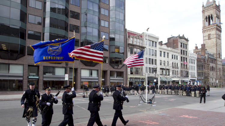 Officers march into position near the blast site on Boylston Street between Dartmouth and Exeter Streets near the Boston Marathon finish line Monday, April 22, 2013 in Boston. Federal investigators formally released the  finish line bombing crime scene to the city in a brief ceremony at 5 p.m. (AP Photo/Robert F. Bukaty)