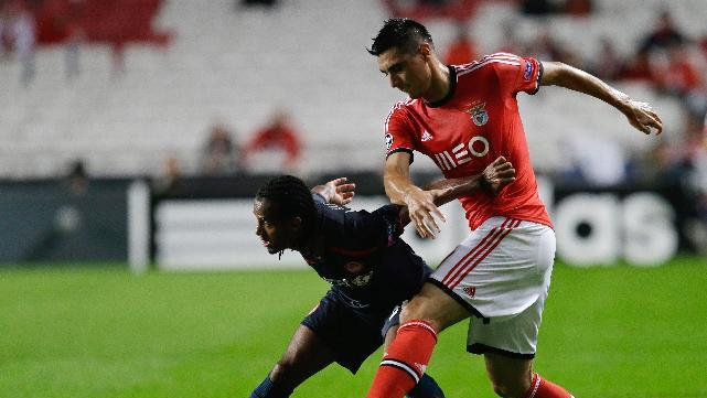 Olympiacos' Leandro Salino, left, fights for the ball with Benfica's Oscar Cardozo during the Champions League group C soccer match between SL Benfica and Olympiacos FC in Lisbon, Wednesday, Oct. 23, 2013