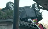 Car Crashes Upside Down On To Roof Of House