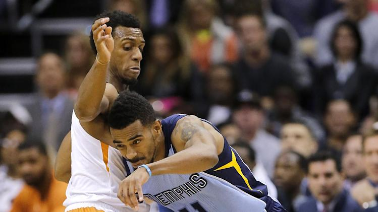 Phoenix Suns' Ish Smith, left, defends against  Memphis Grizzlies' Mike Conley during the second half of an NBA basketball game on Thursday, Jan. 2, 2014, in Phoenix. The Grizzlies won 99-91