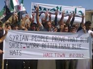 A photo released by the Syrian opposition's Shaam News Network shows Syrians at an anti-regime demonstration in Hass in Idlib province. UN monitors have finally reached the site of a massacre in Syria at a second attempt, activists said, as Western powers pressed at the United Nations for sanctions against Damascus