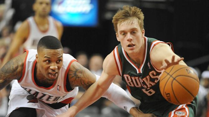 Portland Trail Blazers guard Damian Lillard (0) and Milwaukee Bucks guard Nate Wolters (6) go after a ball during the second half of an NBA basketball game in Portland, Ore., Tuesday, March 18, 2014. The Blazers won the game 120-115 in overtime