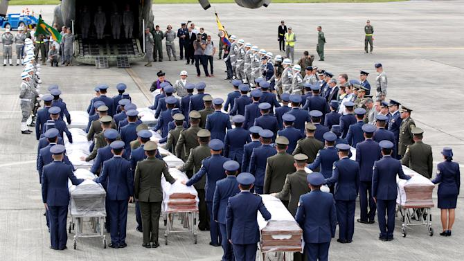 Military personnel unload a coffin with the remains of Brazilian victims who died in an accident of the plane that crashed into the Colombian jungle, at the airport from where the bodies will be flown home to Brazil, in Medellin