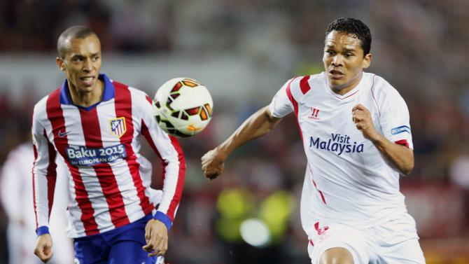 Sevilla's Bacca and Atletico Madrid's Miranda chase the ball during their soccer match in Seville