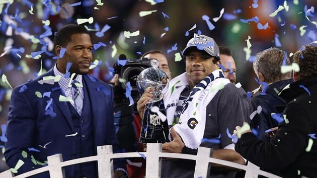 Seattle Seahawks quarterback Russell Wilson holds up the Vince Lombardi Trophy next to newly elected Hall of Fame player Michael Strahan (L) after the...