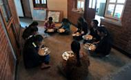 Nepalese Humla children are seen having lunch at their home in Kathmandu. While their classmates come from the country's wealthiest elite, these children were rescued seven years ago, dirty and sick, from a cowshed on the edge of the capital