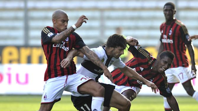 Parma's Carvalho Amauri, center, competes for the ball with AC Milan's Nigel De Jong of Netherlands, left, and Kevin Constant of Guinea, during their Serie A soccer match at Parma's Tardini stadium, Italy, Sunday, Oct. 27, 2013