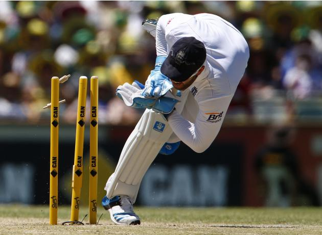 England's Prior attempts to take an unsuccessful run out wicket of Australia's Warner during the third Ashes test cricket match in Perth