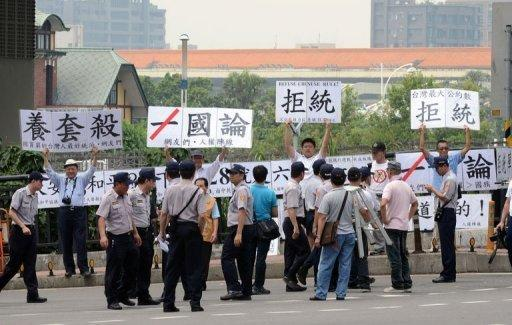"Anti-China activists display placards reading, ""refuse  unificiation with China"""