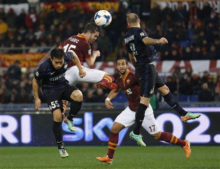 AS Roma's Pjanic jumps for the ball with Inter Milan's Nagatomo and Palacio during their Italian Serie A soccer match at the Olympic stadium in Rome