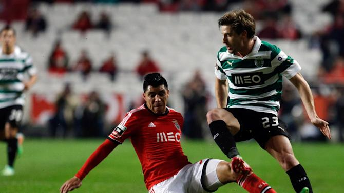 Benfica's Enzo Perez, from Argentina, left, fouls Sporting's Adrien Silva during their Portuguese league soccer match Tuesday, Feb. 11 2014, at Benfica's Luz stadium in Lisbon