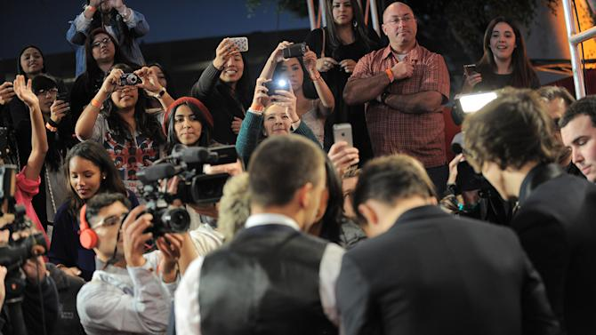 "Fans take pictures as One Direction arrives at the ""The X Factor"" season finale results show at CBS Television City on Thursday, Dec. 20, 2012, in Los Angeles. (Photo by Jordan Strauss/Invision/AP)"