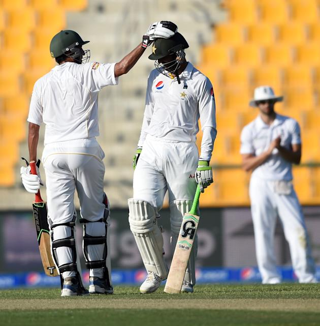 Pakistan' Younis Khan congratulates batsman Shoaib Malik for his century against  England during first day of first test match at Zayed Cricket Stadium in Abu Dhabi, United Arab Emirates, Tuesday,