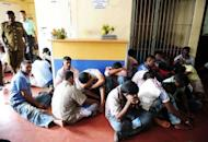 Arrested Sri Lankan men sit inside the police station after authorities cracked down on. Police detained 113 men who were trying to illegally leave the island for Australia along with six men who carried out the would-be illegal boat operation