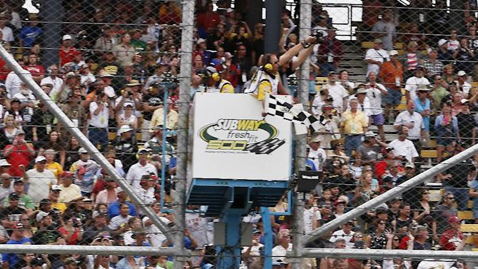 Carl Edwards takes the checkered flag to win the NASCAR Sprint Cup Series auto race, Sunday, March 3, 2013, in Avondale, Ariz. (AP Photo/Ross D. Franklin)