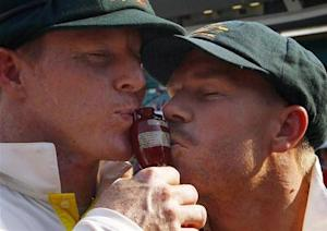 """Australia's Chris Rogers (L) and David Warner kiss the """"Replica Ashes Urn"""" as they celebrate winning the fifth Ashes cricket test against England at the Sydney Cricket Ground January 5, 2014. REUTERS/David Gray/Files"""