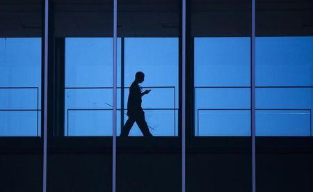 A student uses his mobile phone as he walks inside the Engineering building at the University of Waterloo