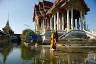 A Buddhist monk cleaning up an area at a temple inundated by flood waters in Don Muang district, in Bangkok, in 2011. Deadly floods, power blackouts and traffic gridlock -- many of Asia's biggest cities are buckling under the strain of rapid economic development, extreme weather and an exodus from the countryside