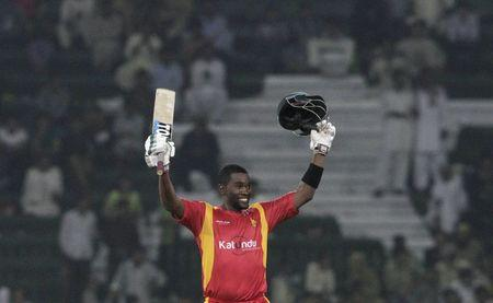 Zimbabwe's captain Elton Chigumbura celebrates after scoring 100 runs during the first One Day International cricket match between Pakistan and Zimbabwe at the Gaddafi Cricket Stadium in Lahore
