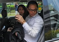 Former Singapore's Central Narcotics Bureau head Ng Boon Gay (R) and his wife leave the subordinate court after his hearing in Singapore. A key state witness gave a graphic account of intimate relations with the Ng, accused of demanding sex for favours in government supply contracts
