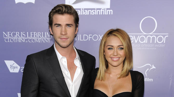 "FILE - In this June 27, 2012 file photo, actor Liam Hemsworth, left, an honoree at the Australians in Film 8th Annual Breakthrough Awards, poses with his fiance Miley Cyrus on the red carpet in Los Angeles. Representatives for both celebrities confirmed they have called off their engagement. They met on the set of 2010's ""The Last Song."" (Photo by Chris Pizzello/Invision/AP, File)"