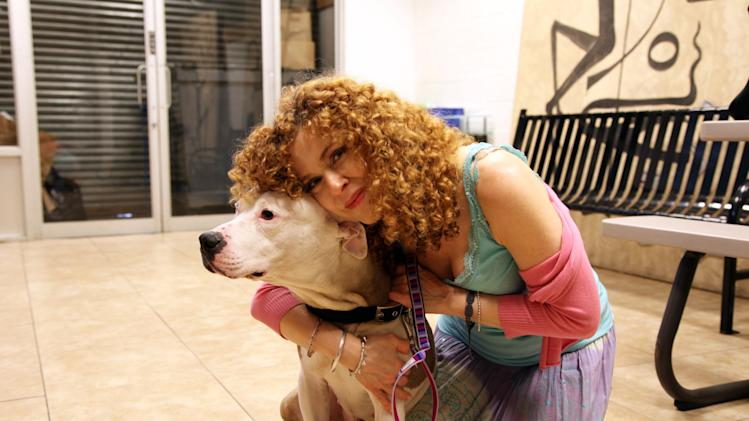 This July 8, 2013 photo shows actress Bernadette Peters with Chili, a 9-year-old Staffordshire Bull Terrier, at the Brooklyn Animal Resource Coalition in the Williamsburg section of the Brooklyn borough of New York. Chili will be part of Saturday's Broadway Barks adopt-a-thon near Times Square. (AP Photo/Mark Kennedy)