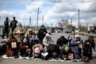 Women pray for peace near a regional administration building that was seized by armed pro-Russian activists in the eastern Ukrainian town of Slovyansk, Ukraine, Monday, April 14, 2014. A pro-Russian mob stormed a Ukrainian police station in Horlivka, another city near the Russian border. Later in the day, armed men in masks also seized control of a military airport outside the city of Slovyansk, also in the Donetsk region bordering Russia. (AP Photo/Evgeniy Maloletka)